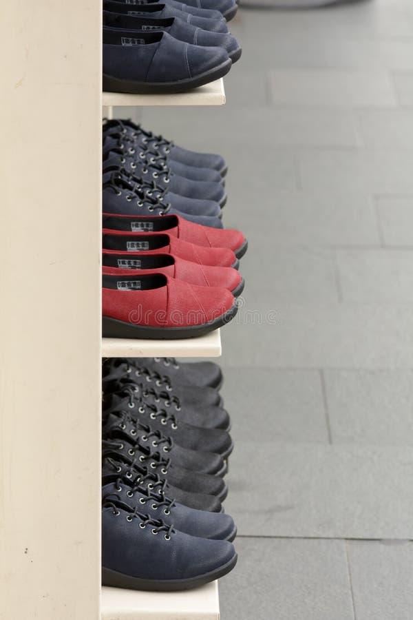 Reihen von Schuhen auf Regalaußenseitenshop lizenzfreie stockfotografie