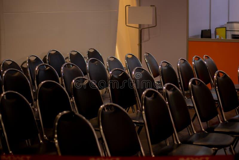 Reihen von schwarzen Stühlen mit Anschlagtafelhintergrund stockbild