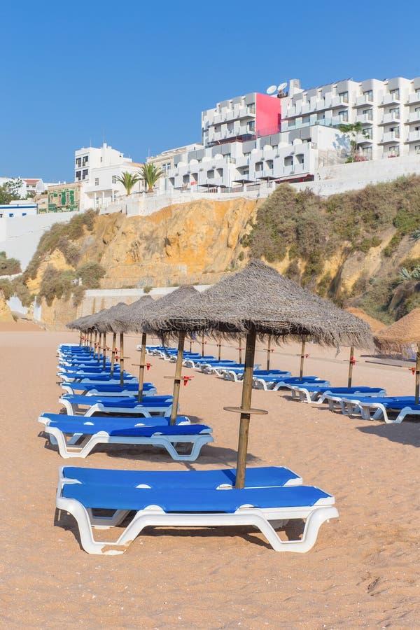 Reihen von Strandbetten mit mit Stroh gedeckten Regenschirmen lizenzfreies stockfoto