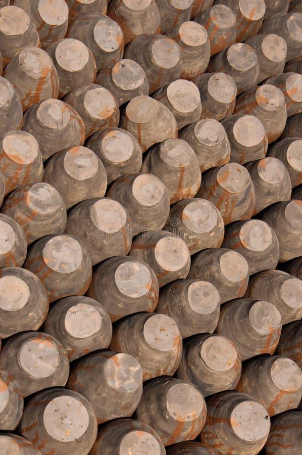 Reihen von Töpfen, Unterseiten oben, Hintergrund Keramische Tonwaren im Töpfer lizenzfreie stockfotografie