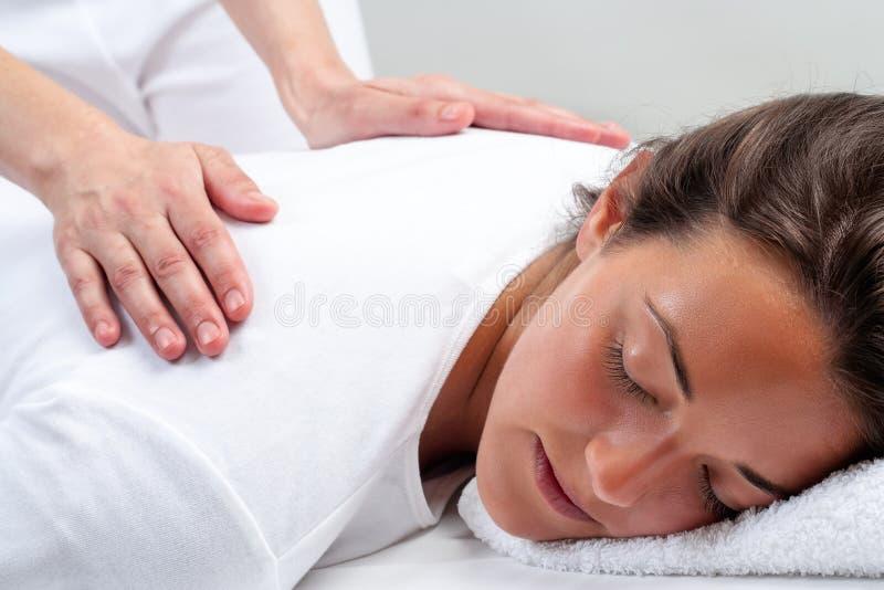 Reikitherapeut die behandeling op vrouw doen stock afbeeldingen