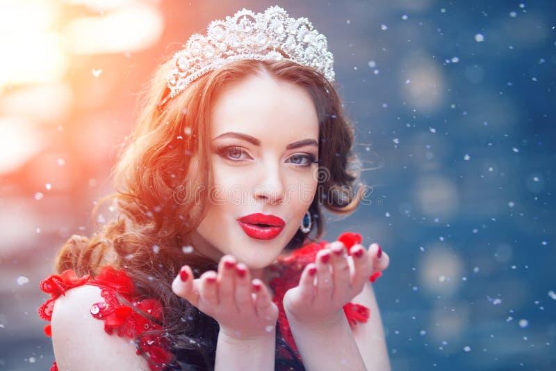 Reina de la nieve en rojo Mujer del invierno en corona en un vestido y un rojo rojos fotos de archivo