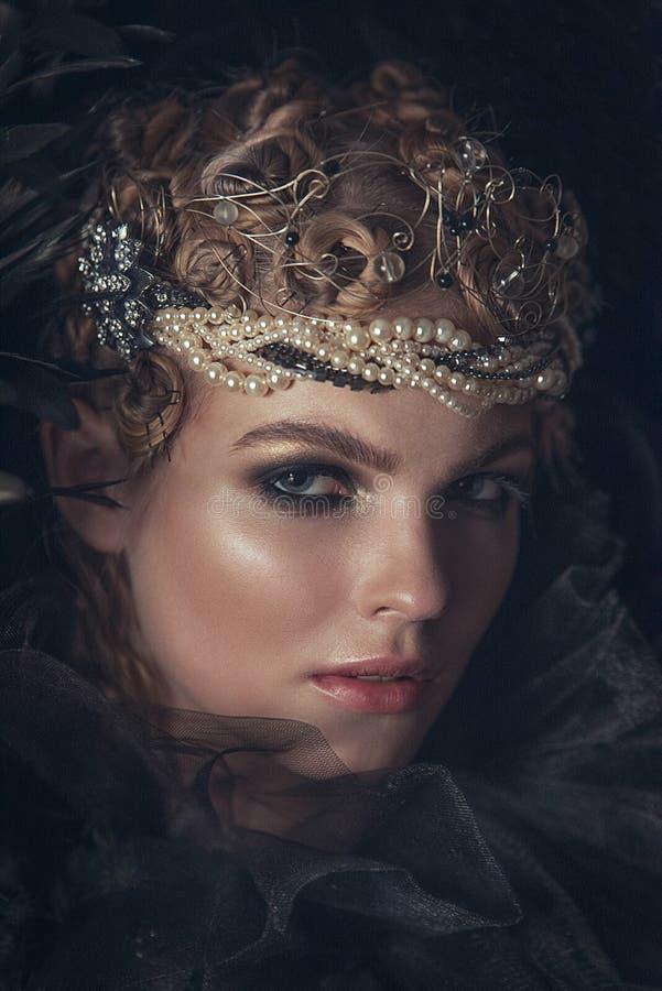 Reina de la oscuridad en traje negro de la fantasía en fondo gótico oscuro Modelo de la belleza de la alta moda con maquillaje os imagen de archivo