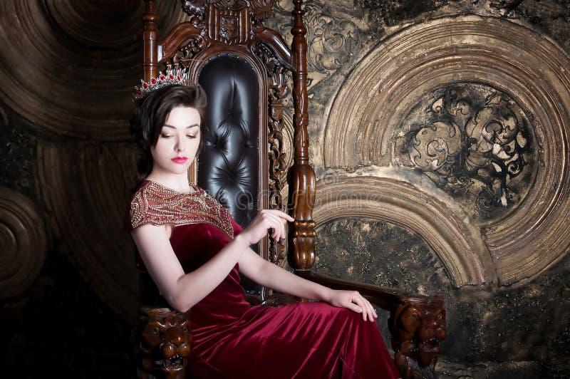Reina en el vestido rojo que se sienta en el trono S?mbolo del poder y de la riqueza fotos de archivo