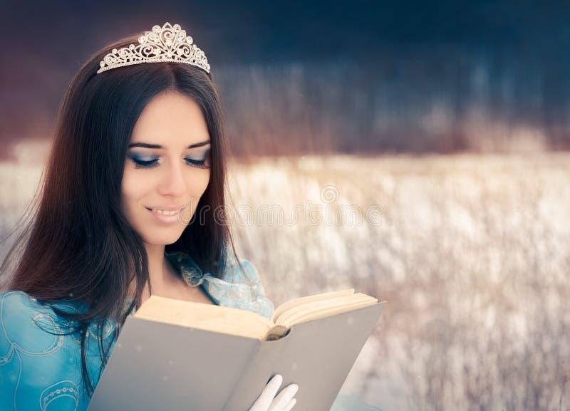 Reina hermosa de la nieve que lee un libro foto de archivo