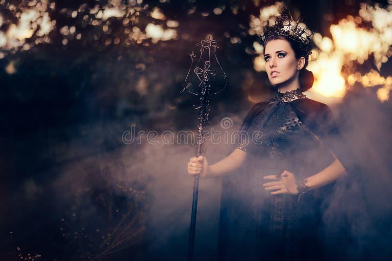 Reina malvada que sostiene el cetro en Misty Forest foto de archivo libre de regalías