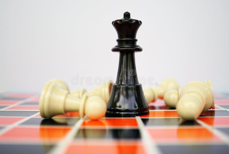 Reina negra del ajedrez con los empeños blancos foto de archivo