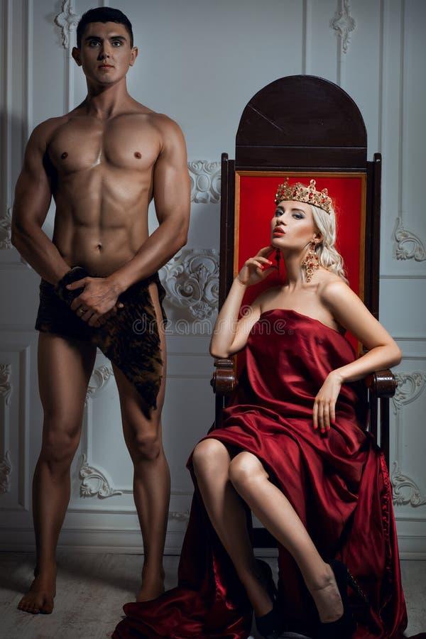 Reina que se sienta en un trono Cerca está un esclavo atlético foto de archivo
