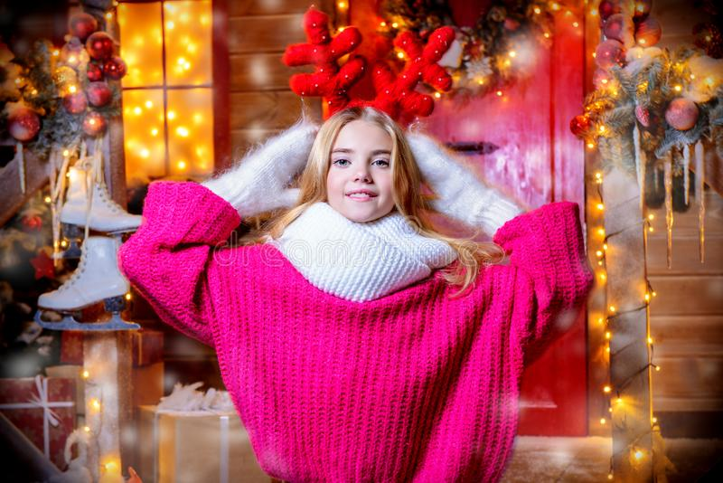 With reindeer antlers. Pretty child girl is standing near his house decorated for Christmas with reindeer antlers on the head. Merry Christmas and Happy New Year royalty free stock photos