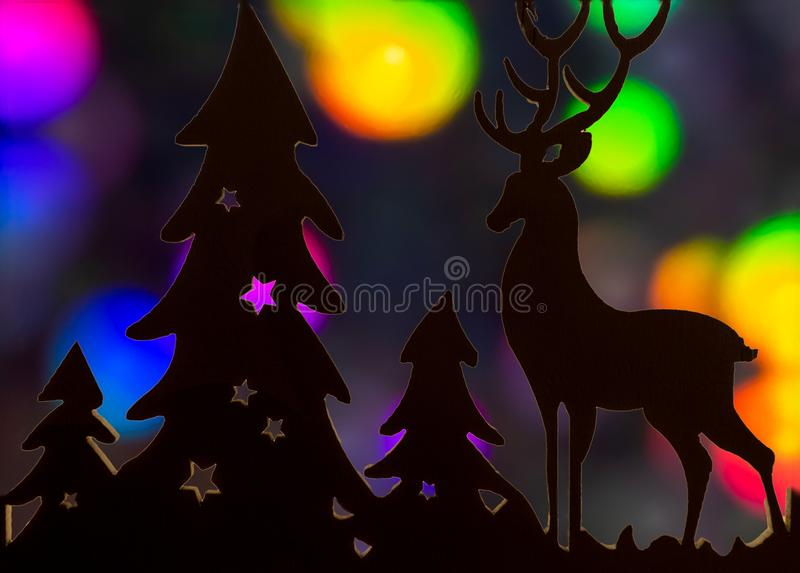 Reindeer and christmas tree cutout silhouette with multicolored bokeh backdrop royalty free stock images