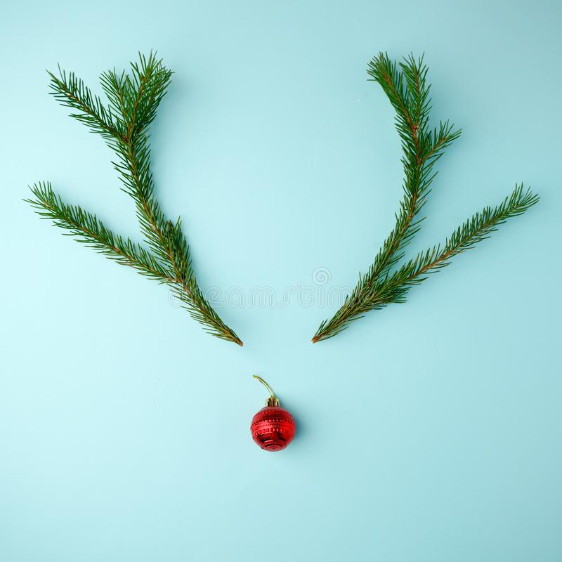 Reindeer face made of Christmas decoration and pine branches on blue background. Minimal christmas concept. Flat lay, top view. royalty free stock photos