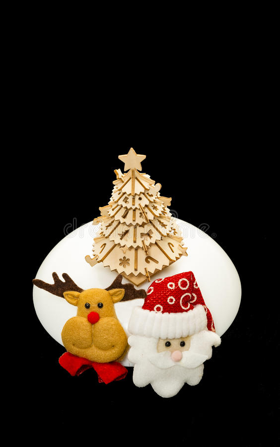 Reindeer and Santa face near wooden Christmas tree. Isolated from black background royalty free stock images