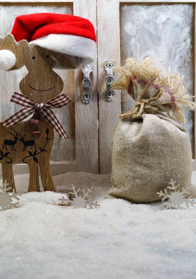 Reindeer in santa hat and a bag of Christmas presents. The magic of Christmas stock image