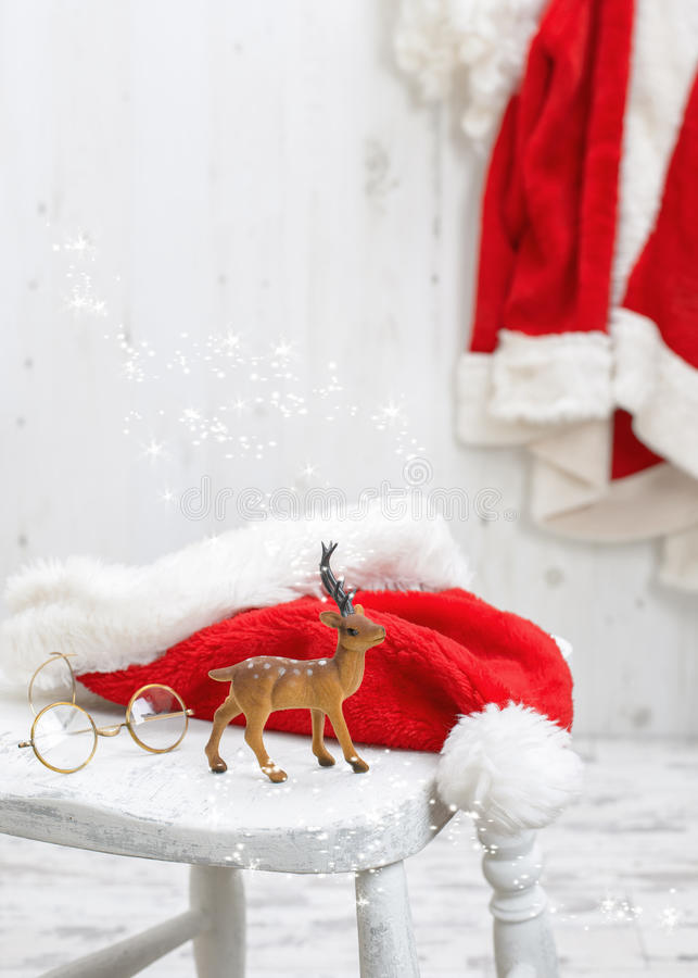 Reindeer With Santa Hat. Reindeer with santa and spectacles hat on white stool royalty free stock photo