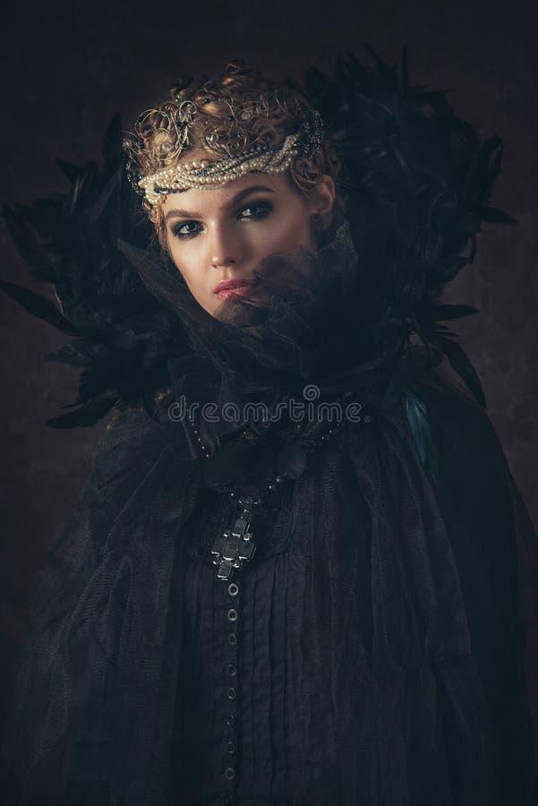 Reine d'obscurité dans le costume noir d'imagination sur le fond gothique foncé Modèle de beauté de haute couture avec le maquill photos libres de droits