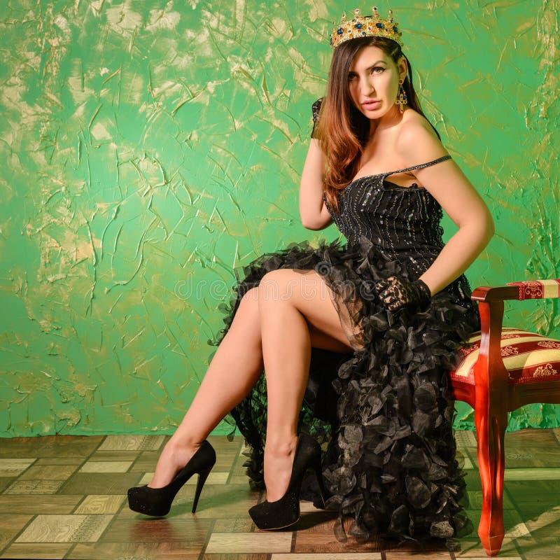 Reine dans la robe et la couronne de soirée noires sur sa tête photo stock