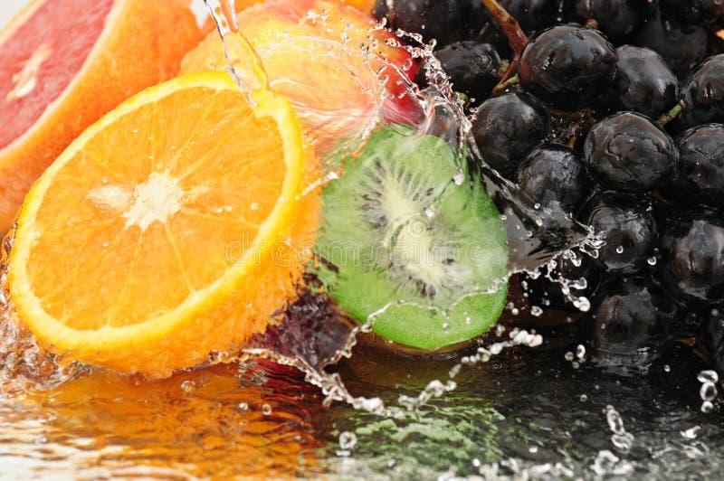 Reine Frucht in einem Spray des Wassers lizenzfreie stockfotos