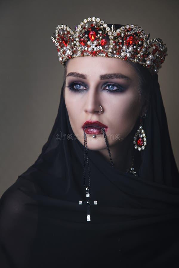 Reine noire dans une couronne et avec un crucifix image libre de droits