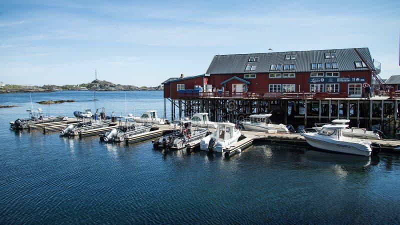 Reine, Noorwegen - Juni 2, 2016: Traditionele vissersboot met rode rorbu visserijhuizen op Lofoten-eilanden in Noorwegen royalty-vrije stock fotografie