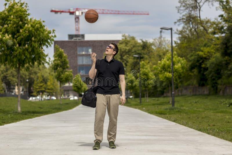 Reine Spekulation des zufällig gekleideten Mannes mit einer Basketball-und Turnhallen-Tasche stockfoto