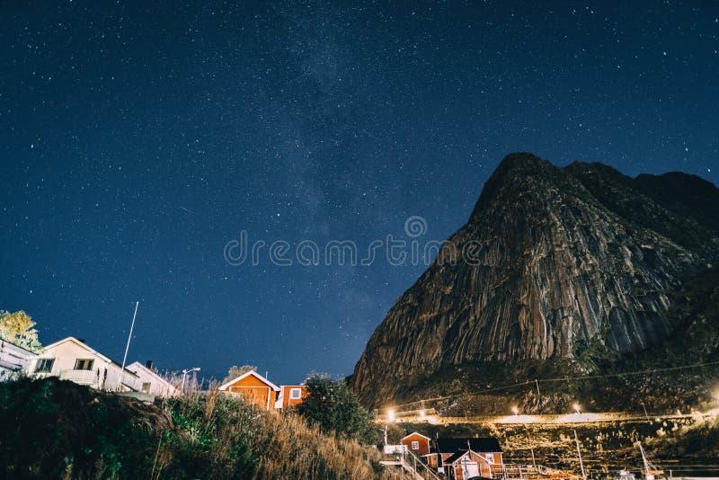 Reinebringen avec la manière laiteuse au-dessus des montagnes Village des îles de Reine Hamnoy Sakrisoy Lofoten Paysage de nuit a photos libres de droits
