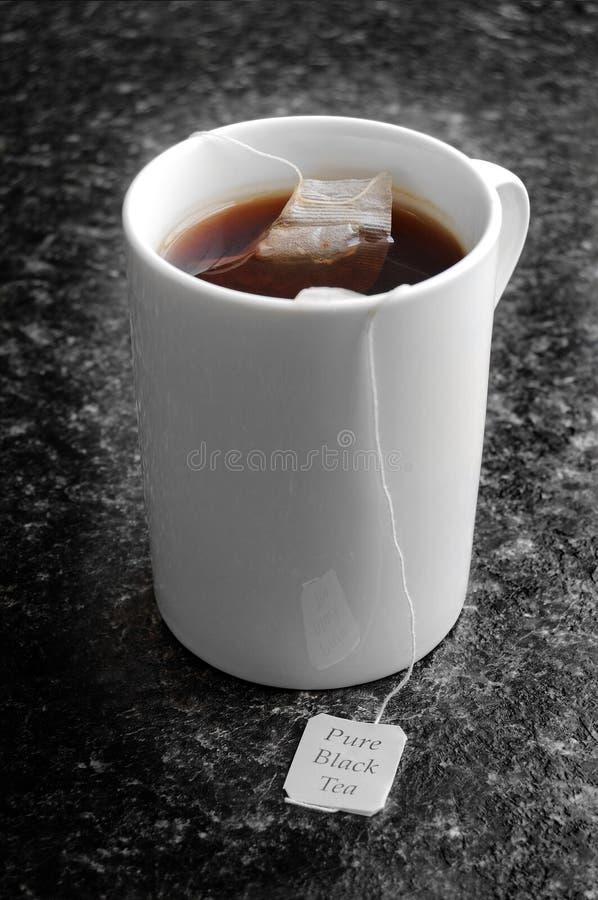 Reiner schwarzer Tee in einem Becher lizenzfreie stockfotos