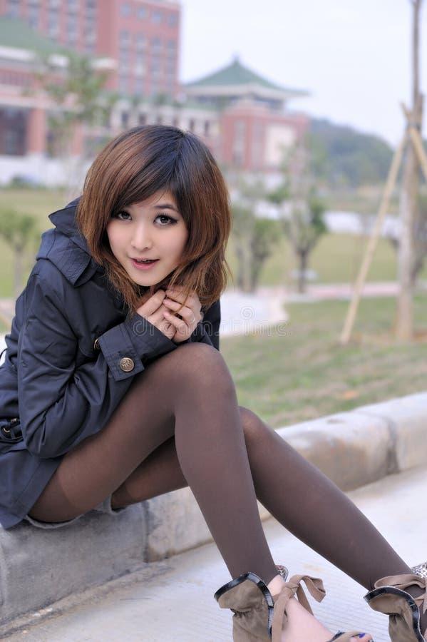 Reines schönes asiatisches Mädchen, das auf der Straßenseite sitzt stockbilder