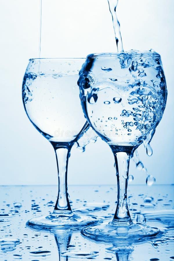 Reines Wasser, das in Gläser gießt lizenzfreies stockfoto