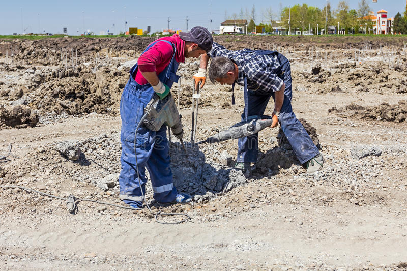 Reinforced concrete pillar picking from foundation of a new building. Zrenjanin, Vojvodina, Serbia - April 24, 2015: Construction workers are holding jackhammer royalty free stock image