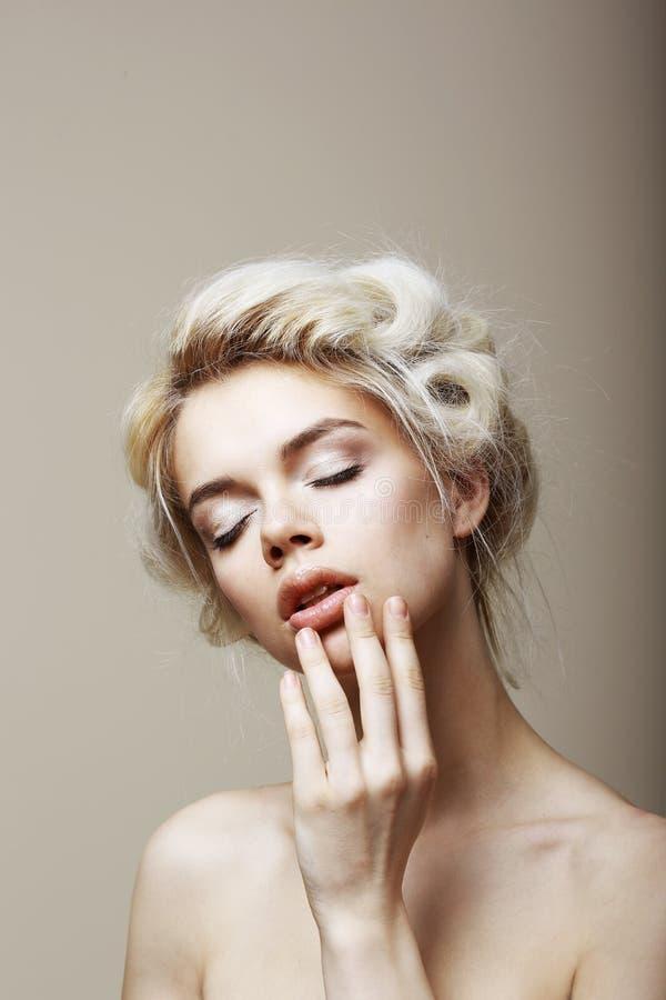 Reinheit. Sinnliche romantische blonde Frau mit den geschlossenen Augen, die ihr Gesicht berühren. Muse lizenzfreie stockbilder