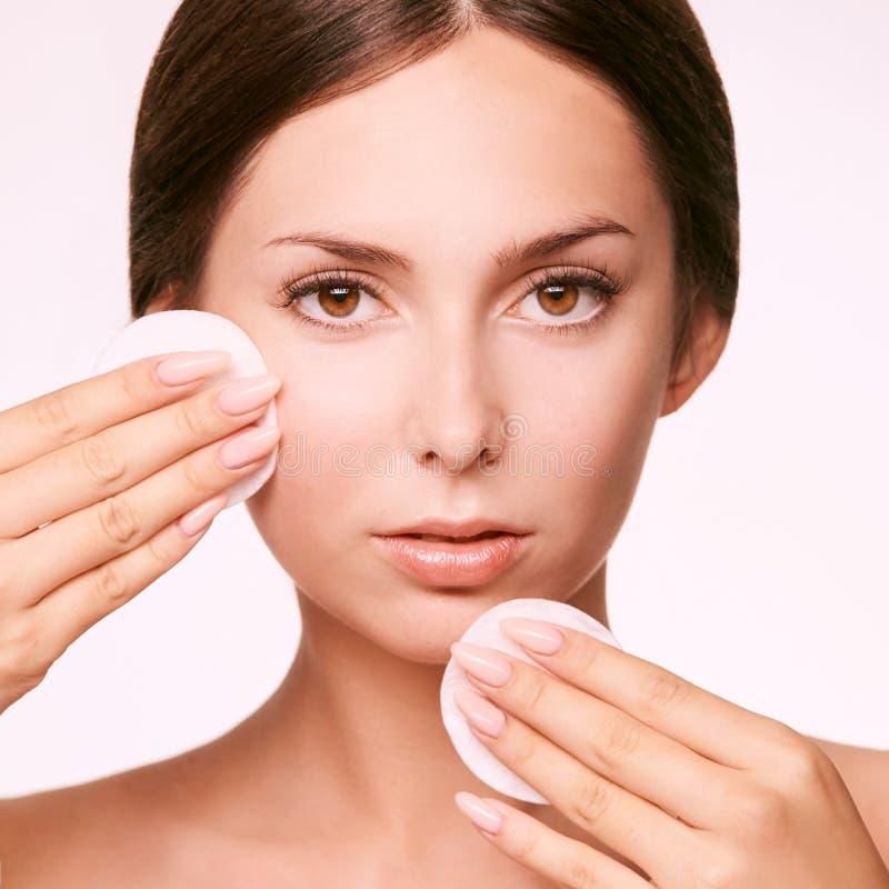 Reinigend gezichts wasing tonicum Demakeup verwijder mascara Katoenen stootkussenhand stock foto