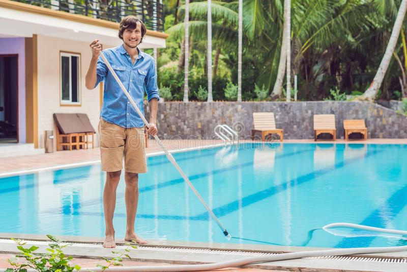 Reiniger des Swimmingpools Mann in einem blauen Hemd mit der Reinigungsanlage für Schwimmbäder, sonnig lizenzfreie stockbilder