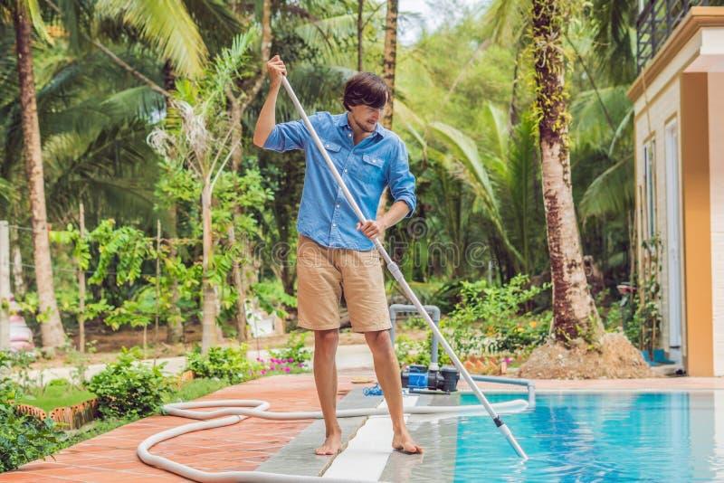 Reiniger des Swimmingpools Mann in einem blauen Hemd mit der Reinigungsanlage für Schwimmbäder, sonnig stockfotos