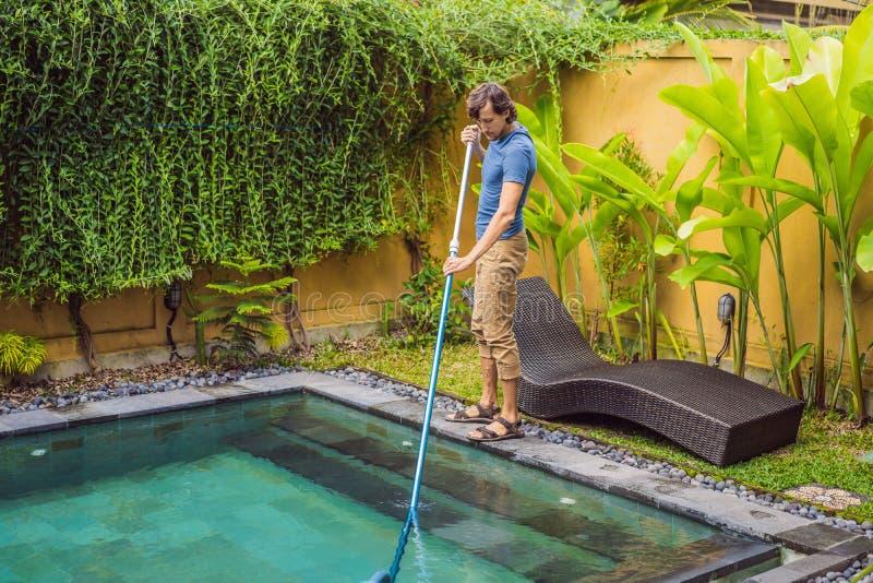 Reiniger des Swimmingpools Mann in einem blauen Hemd mit Reinigungsanlage f?r Schwimmb?der Poolreinigungsdienstleistungen stockbilder