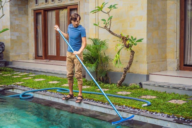 Reiniger des Swimmingpools Mann in einem blauen Hemd mit Reinigungsanlage f?r Schwimmb?der Poolreinigungsdienstleistungen stockfotografie