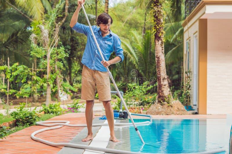 Reinigingsmachine van het zwembad Mens in een blauw overhemd met het schoonmaken van materiaal voor zonnige zwembaden, royalty-vrije stock foto's