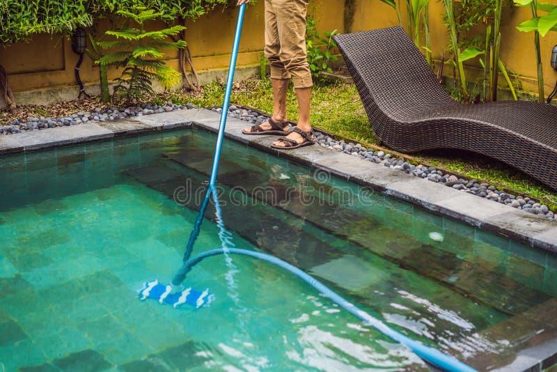 Reinigingsmachine van het zwembad Mens in een blauw overhemd met het schoonmaken van materiaal voor zwembaden De pool schoonmaken stock foto