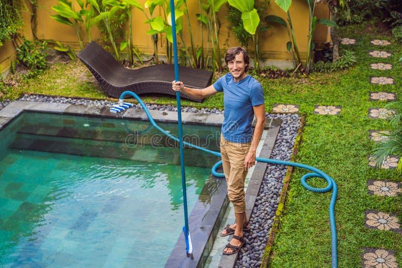 Reinigingsmachine van het zwembad Mens in een blauw overhemd met het schoonmaken van materiaal voor zwembaden De pool schoonmaken royalty-vrije stock foto