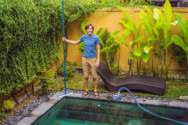Reinigingsmachine van het zwembad Mens in een blauw overhemd met het schoonmaken van materiaal voor zwembaden De pool schoonmaken royalty-vrije stock afbeelding