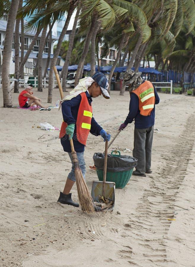 Reinigingsmachines die het strand van Si Racha van huisvuil en afval ontruimen stock foto