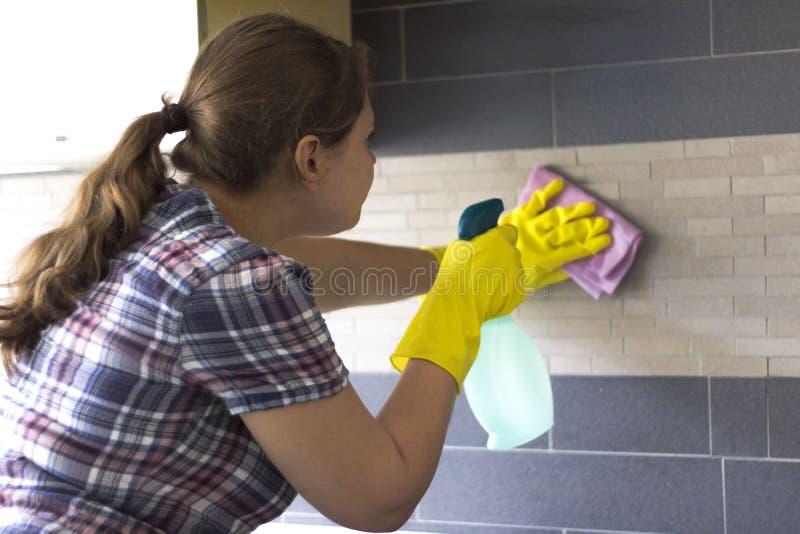 Reinigung des jungen Mädchens in der Küche stockfoto