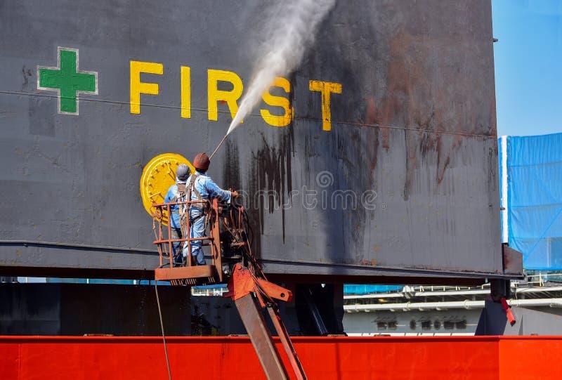 Reinigung am Lukendeckelschiff und am Säubern des Frachtschiffs im Schwimmdock durch Hochdruckwasserstrahl stockfotografie