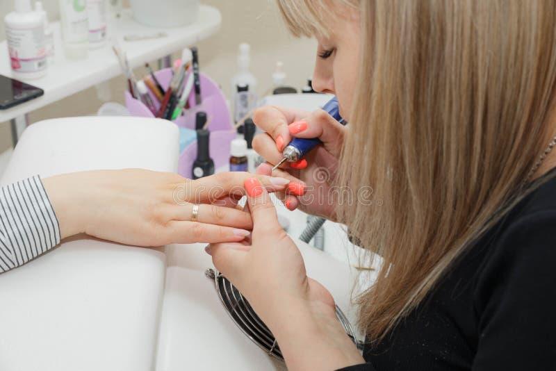 Reinigung und Ausrichtung der Schleifmaschine des Häutchens an der Wurzel der Nägel auf den Händen stockbild