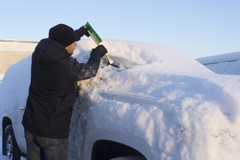 Reinigungsauto des jungen Mannes vom Schnee lizenzfreies stockbild