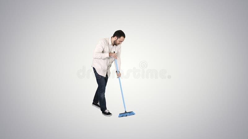 Reinigungsboden des jungen Mannes mit Bürste auf Steigungshintergrund lizenzfreie stockbilder