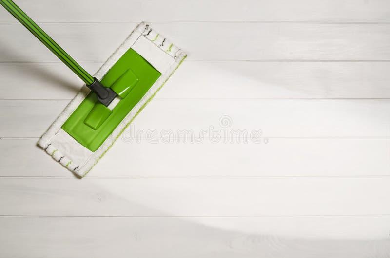 Reinigungsboden mit Draufsicht des Mops über weißen hölzernen Hintergrund stockbild