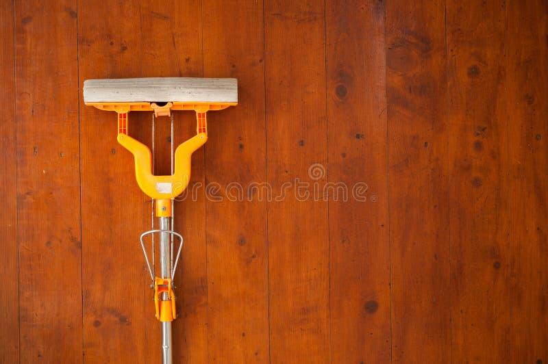 Reinigungsbretterboden mit Orange machte Mopp nass stockfoto