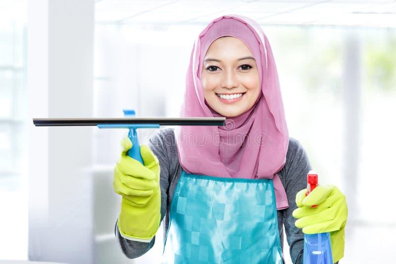 Reinigungsfenster der jungen Frau mit Gummiwalze und Reinigung sprühen stockbilder