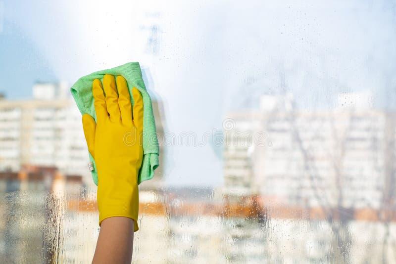 Reinigungsfenster mit speziellem Lappen Reinigungsfrau, die das Reinigungsspray-Flaschenschießen glücklich und das Lächeln zeigt lizenzfreies stockbild