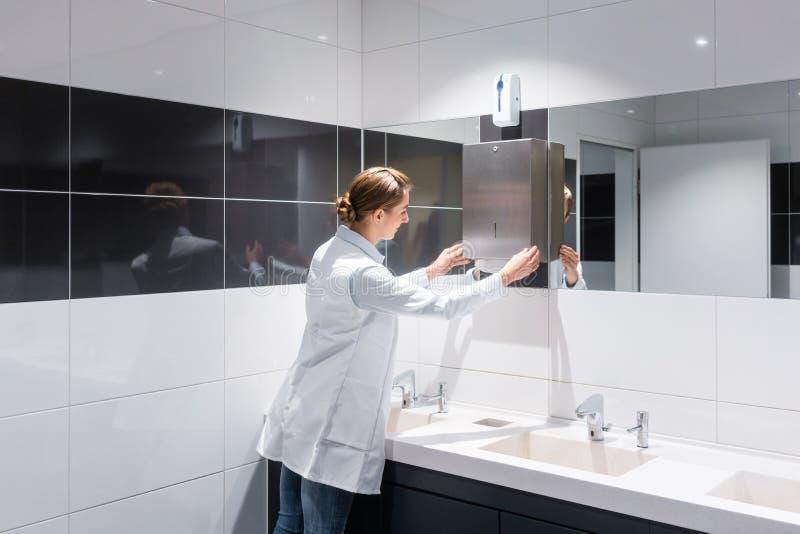 Reinigungsfrau, die öffentlich Toilette der Papierhandtücher wieder füllt lizenzfreies stockfoto